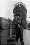 """02/06/1964 <br /> 06/02/1964<br /> 02 June 1964<br /> Mr. C.M. Grace, Engineer Superintendent , Palgrave Murphy Shipping Ltd., at the Liffey Dockyard with the """"City of Cork"""" in background."""