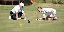 © Licensed to London News Pictures. 14/08/2013. Surbiton, UK Ian Lines, England with referee watching. People participate in the14th World Association Croquet Championship at the Surbiton Croquet Club, Kingston upon Thames on the 14th August 2013. The Final will be played on Sunday 18th August. 80 competitors from 20 countries are taking part. Photo credit : Mike King/LNP