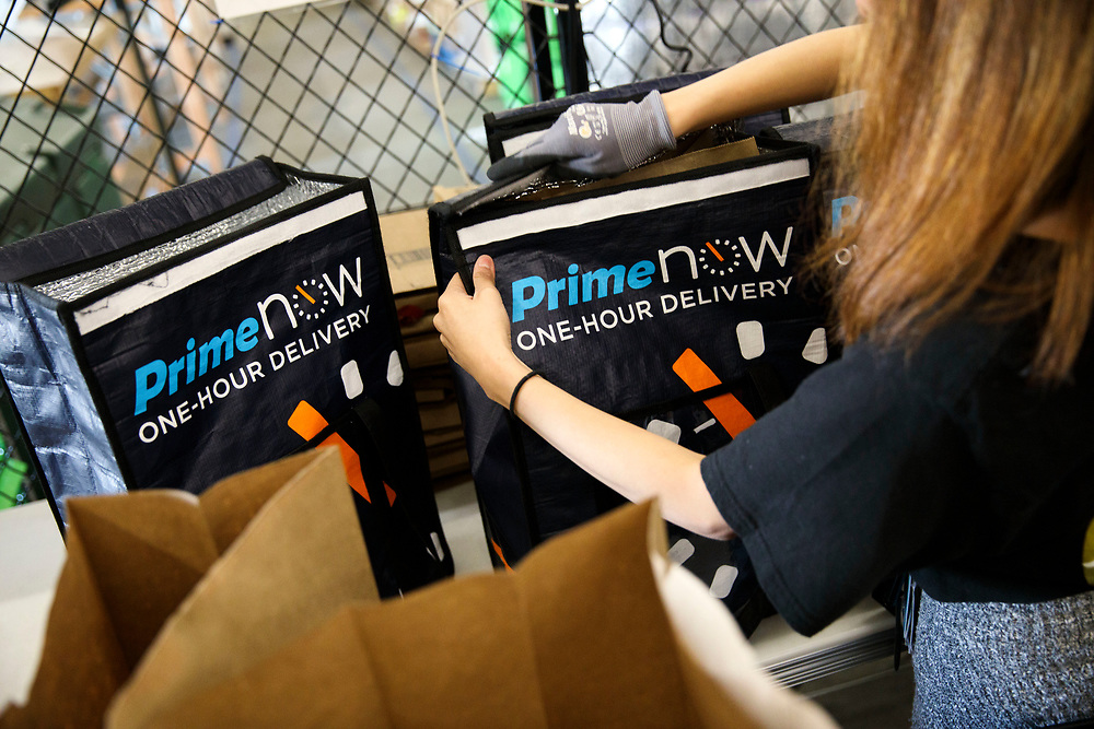 An Amazon associate places bags containing cold items into dry ice cooled delivery bags at the Amazon.com Inc. Prime Now fulfillment center warehouse on Monday, March 27, 2017 in Los Angeles, Calif. The warehouse can fulfill one and two hour delivery to customers. Complex supply chains such as Amazon's and e-commerce trends will impact city infrastructure and how things move through cities. © 2017 Patrick T. Fallon