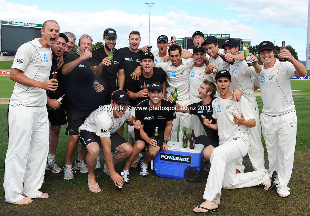 New Zealand players and coaching staff pose for a team photo in the middle of the wicket ater a famous victory over Australia on Day 4 of the second cricket test between Australia and New Zealand Black Caps at Bellerive Oval in Hobart, Monday 12 December 2011. Photo: Andrew Cornaga/Photosport.co.nz