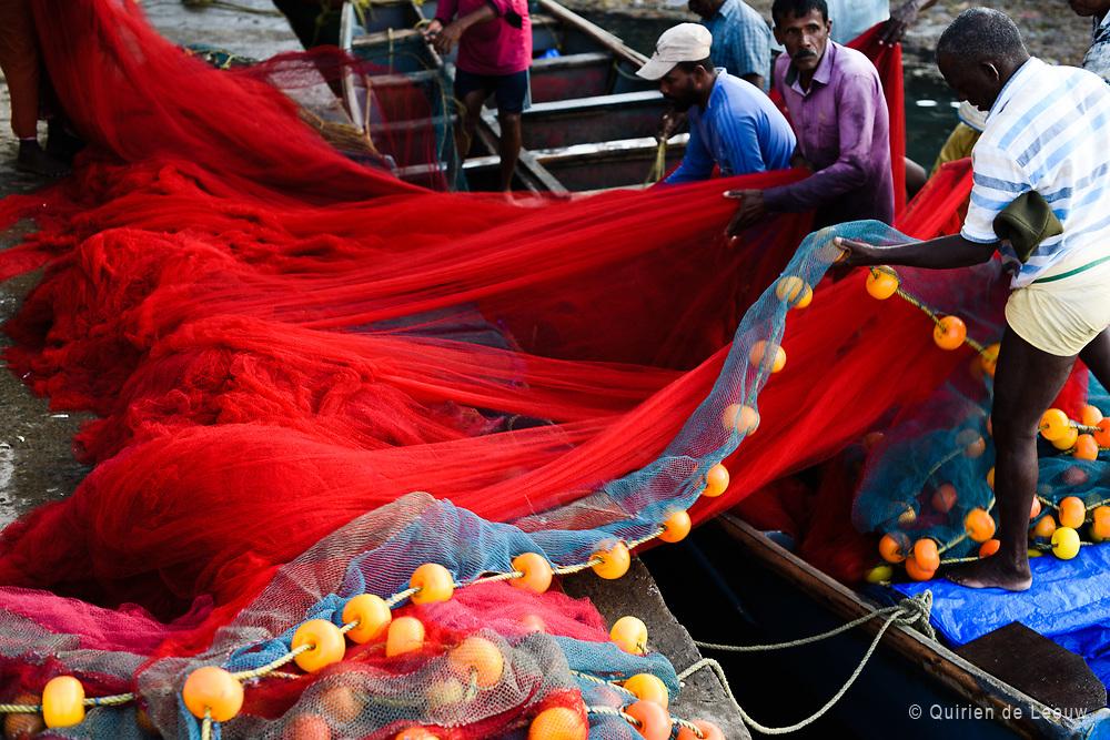 Vissers vouwen visnet in de haven bij Kochi