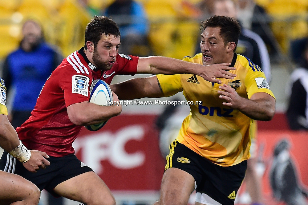 Tom Taylor of the Crusaders is tackled by Jack Lam of the Hurricanes during the Super Rugby - Hurricanes v  Crusaders rugby match at the Westpac Stadium in Wellington, New Zealand on the 28th of June 2014. Photo: Marty Melville/www.Photosport.co.nz