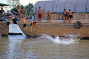 THAILAND, CHAO PHRAYA RIVER. teak rice barges and boys swimming