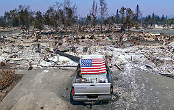 October 12, 2017 - California, U.S. - A truck displays an American flag on it's rear window in the devastated Coffey Park neighborhood in Santa Rosa, Calif. The wildfires are still raging and now the worst in state history. (Credit Image: © Hector Amezcua/Sacramento Bee via ZUMA Wire)
