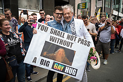 """© Licensed to London News Pictures . 29/08/2015 . Manchester , UK . The actor , SIR IAN MCKELLEN , poses with a fan with a """" YOU SHALL NOT PASS WITHOUT A BIG GAY HUG """" banner , as he leads the 2015 Manchester Pride parade . Photo credit : Joel Goodman/LNP"""