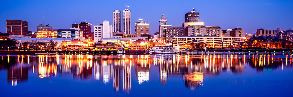 Peoria Illinois skyline at night panorama photo of downtown Peoria city buildings reflection on the Illinois River. Panoramic picture ratio is 1:3.