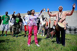 29 August 2013. Lower 9th Ward, New Orleans, Louisiana.<br /> Hurricane Katrina memorial 8 years later. <br /> Debera Reed pours symbolic water on the levee as local residents gather in the Lower 9th ward to remember those who perished in the storm 8 years ago.<br /> Photo; Charlie Varley