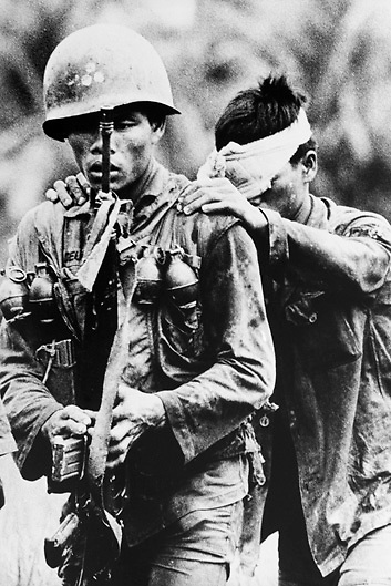 Vietnamese Army soldier guides wounded comrade to waiting evacuation helicopter during fighting against Viet Cong forces in the Delta south of Saigon during the Vietnam War