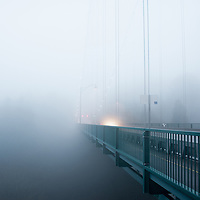 Heavy fog on the Lions Gate Bridge with light and trees faint in the distance, disappearing.