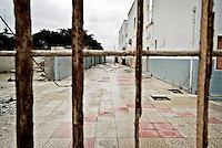 """L'ex centro di permanenza temporanea """"Casa Regina Pacis"""" a San foca (LE) ormai in disuso, visto da dietro la cancellata d'ingresso. 21/02/2010 (PH Gabriele Spedicato)..I Centri di permanenza temporanea (CPT), ora denominati Centri di identificazione ed espulsione (CIE), sono strutture istituite in ottemperanza a quanto disposto all'articolo 12 della legge Turco-Napolitano (L. 40/1998) per ospitare gli stranieri """"sottoposti a provvedimenti di espulsione e o di respingimento con accompagnamento coattivo alla frontiera"""" nel caso in cui il provvedimento non sia immediatamenti eseguibile."""