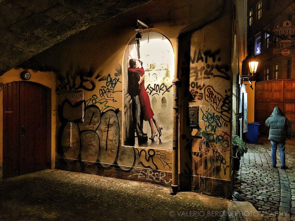 A door, a mural, a man under Charles Bridge in Prague.