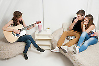 Young woman playing guitar with friends sitting on sofa
