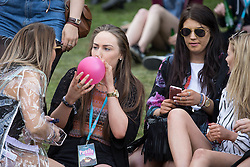 © Licensed to London News Pictures .06/06/2015. Manchester , UK.  A woman breathes from a balloon at The Parklife 2015 music festival in Heaton Park , Manchester . Photo credit : Joel Goodman/LNP