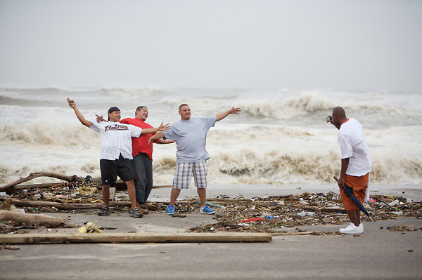 Stock photo of four men taking pictures on a Galveston beach during Hurricane Ike