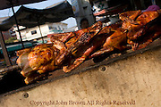 Chicken destined for a a mobile food cart is slowly roasting over hot coals on a city street in Kampong Cham, Cambodia.
