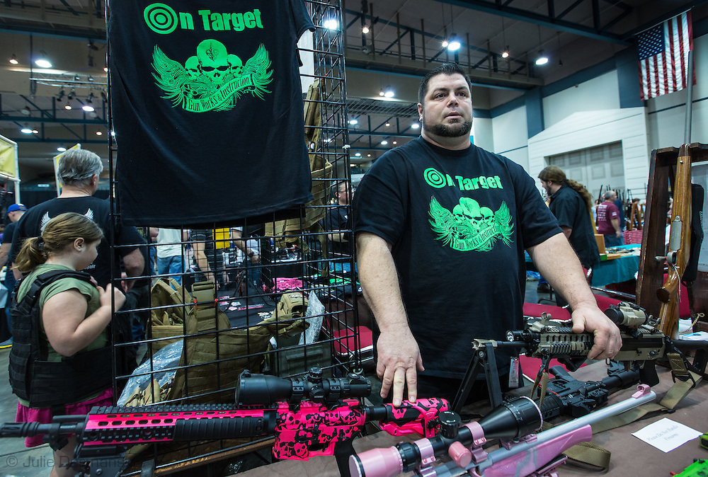 December 16th,  John Gauthier owner of On Target, with his guns custom painting guns resting his hands on custom built   AR 15s, at a<br /> gun show at the Pontchartrain Center in Kenner Louisiana held by Great Southern Gun and Knife Shows L.L. C. .Gauthier is a firearms instructor and makes custom made guns.  Gun sales have increased since the school shooting massacre in Sandy Hook Connecticut, especially AR 15s  ( one of the guns used by Adam Lanza, the killer) as gun owners fear new legislature will soon regulate sales of such guns.