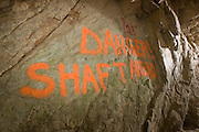 A spray painted warning giving notice of a dangerous vertical shaft inside the abandoned 'Falling Man' gold mine. The mine's place name comes from an incident where a man fell into shaft and was severely injured. Coleville National Forest, Washington.