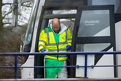 © Licensed to London News Pictures. 09/02/2020. Milton Keynes, UK. A person wearing protective clothing disembarks a coach carrying British evacuees from China after it arrived at Kents Hill Park Training and Conference Centre. A Milton Keynes conference centre is to house evacuees from the Chinese city of Wuhan, the epicentre of the Novel Coronavirus (2019-nCoV) outbreak, the British citizens arrived back on Sunday 9th February and landed at RAF Brize Norton in Oxfordshire and will remain at the conference centre for 14 days to be monitored. Photo credit: Peter Manning/LNP
