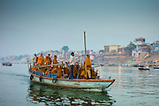 Buddhist monks in boat cruise on River Ganges at Varanasi, Benares, Northern India