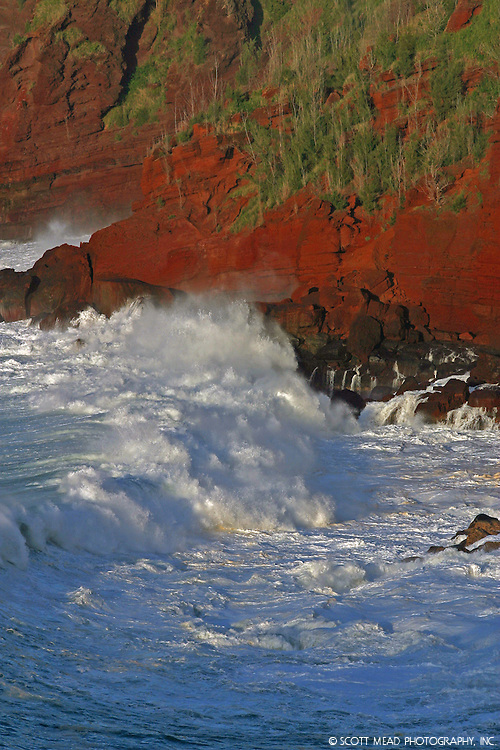 Crashing waves against red cinder cliff from Oneloa Bay, Kapalua, Hawaii