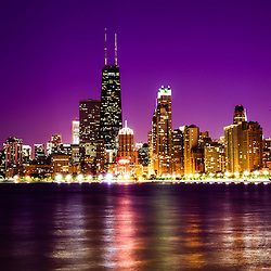 Photo of Chicago skyline at night with a purple sky. Includes the famous John Hancock Center skyscraper one of the tallest buildings in the world. Photo is large high resolution and was taken in 2012.