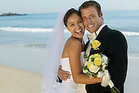 Bride and Groom embracing on beach (portrait)