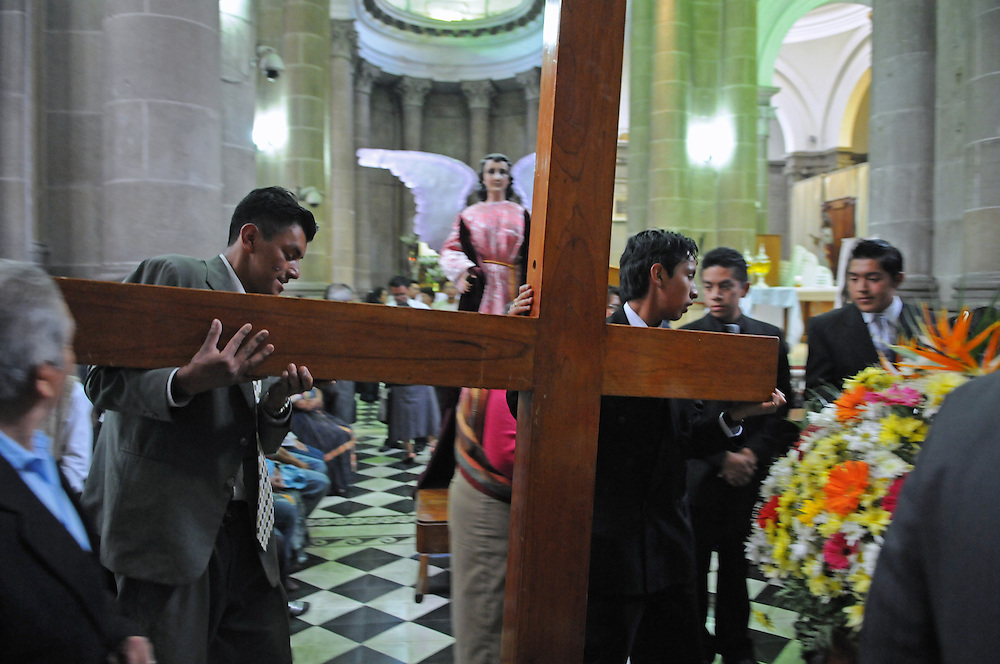 Apr 21, 2011 - Quetzaltenago, Guatemala - Two members of the Nazarene Brotherhood carry a large cross to place on the shoulders of the Jesus of Nazareth statues. The Procession of the Just Judge will take the Saint Statues to the President of the Nazarene brotherhood's home, before being brought back to the Cathedral Friday..(Credit Image: © Josh Bachman/ZUMA Press)