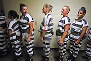 """05 JULY 2001 -- PHOENIX, AZ:  Members of the women chain gang in Maricopa County, Phoenix, AZ, line up in the jail before starting their job of burying people in the county's """"Potter's Field"""" or cemetery for the indigent. Maricopa county sheriff Joe Arpaio claims to have the only women's chain gang in the United States. He has been criticized for the chain gang but claims to be an """"equal opportunity incarcerator."""" He has said that if puts men on a chain gang he will also put women on a chain gang. The women are prisoners in the county jail and volunteer for duty on the chain gang because it gets them out of the jail for six hours a day. The chain gang also buries the county's homeless and indigents. PHOTO BY JACK KURTZ"""
