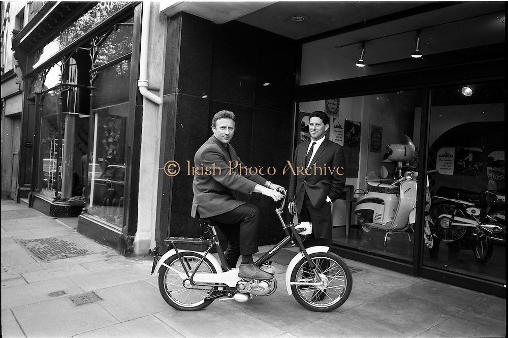"""26/06/1967<br /> 06/26/1967<br /> 26 June 1967<br /> Motoring Enthusiasts Week officially opened by Joe Lynch at the International Trade Promotion Centre, Dublin. Image shows Joe Lynch arriving at the International Trade Promotion Centre on the new Garelli """"Wasp"""" and being greeted by Mr. Patrick McCarthy, Managing Director, Agrati Sales (Ireland) Ltd."""