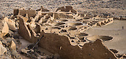 The fun Pueblo Alto Trail overlooks Pueblo Bonito, a monumental public building (Puebloan Great House) occupied from around 828 to 1126 AD, now preserved at Chaco Culture National Historical Park, New Mexico, USA. The huge D-shaped complex of Pueblo Bonito enclosed two plazas with dozens of ceremonial kivas, plus 600 rooms towering 4 and 5 stories above the valley floor. The functions of this building included ceremony, administration, trading, storage, hospitality, communications, astronomy, and burial, but few living quarters. Chaco Culture NHP hosts the densest and most exceptional concentration of pueblos in the American Southwest and is a UNESCO World Heritage Site, located in remote northwestern New Mexico, between Albuquerque and Farmington. From 850 AD to 1250 AD, Chaco Canyon advanced then declined as a major center of culture for the Ancient Pueblo Peoples. Chacoans quarried sandstone blocks and hauled timber from great distances, assembling fifteen major complexes that remained the largest buildings in North America until the 1800s. Climate change may have led to its abandonment, beginning with a 50-year drought starting in 1130. This panorama was stitched from 2 overlapping photos.