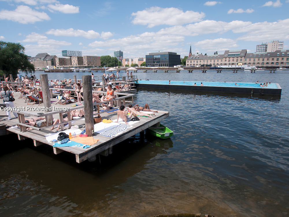 Many people sunbathing and swimming at Badeschiff riverside floating swimming pool and decking on Spree River in Kreuzberg Berlin Germany