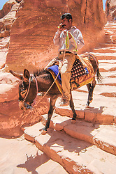 A donkey driver chats on his cellphone as he makes his way down some steps at the rock-cut city complex of Petra, which is nearly 2000 years old.