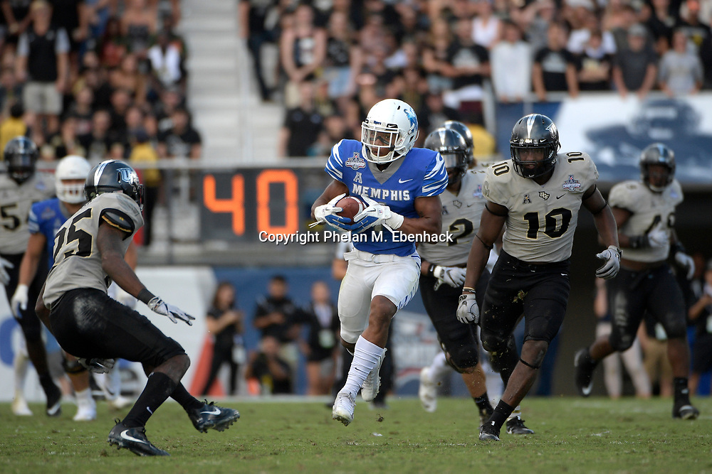 Memphis running back Tony Pollard (1) rushes for yardage between Central Florida defensive back Kyle Gibson (25) and linebacker Titus Davis (10) during the second half of the American Athletic Conference championship NCAA college football game Saturday, Dec. 2, 2017, in Orlando, Fla. Central Florida won 62-55. (Photo by Phelan M. Ebenhack)