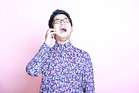 Young Geeky Asian Man in colorful shirt laughing on the phone