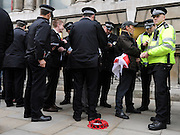 © Licensed to London News Pictures. 11/11/2011. London, UK. Men are searched by police officers after being arrested. Police arrest members of the EDL near the Cenotaph following a Remembrance Day service today (11/11/2011). A large group of EDL members where arrested. Police a. Photo credit : Stephen Simpson/LNP