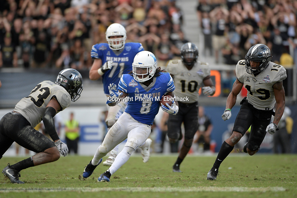Memphis running back Darrell Henderson (8) is pursued by Central Florida defensive back Tre Neal (23), linebacker Titus Davis (10) and defensive back Mike Hughes (19) after rushing for yardage during the second half of the American Athletic Conference championship NCAA college football game Saturday, Dec. 2, 2017, in Orlando, Fla. Central Florida won 62-55. (Photo by Phelan M. Ebenhack)