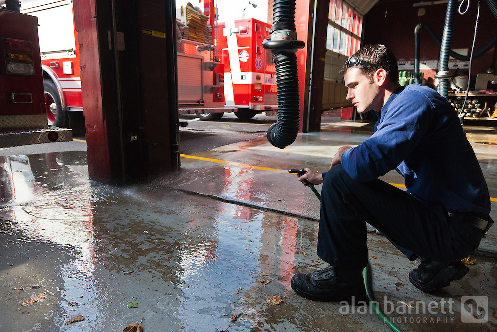 A firefighter hoses down the engine bay floor.