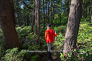 A female hiker walks through a forest on Sucia Island, Washington state.