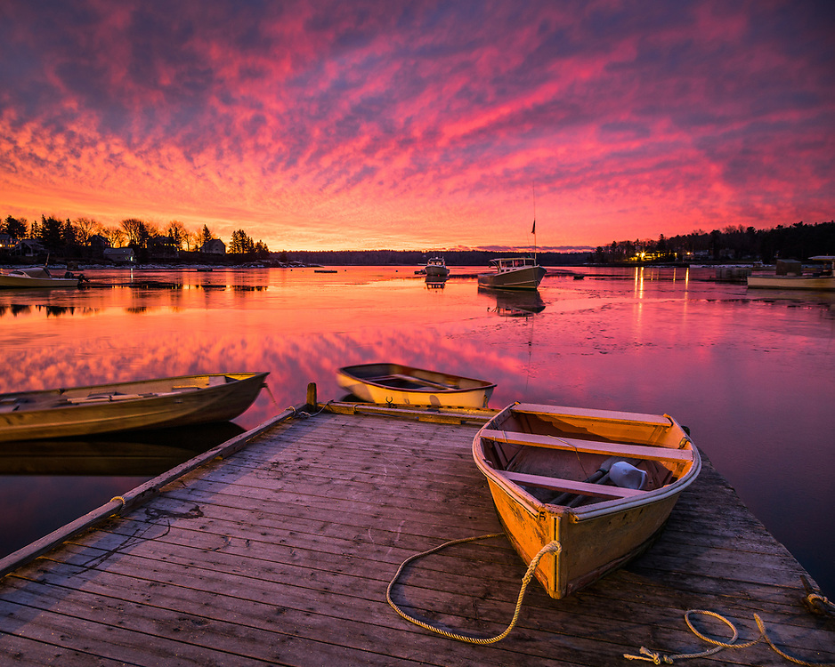 A dinghy sits on the dock in the little fishing village of Round Pond, near Bristol, under an electric sky at sunrise.