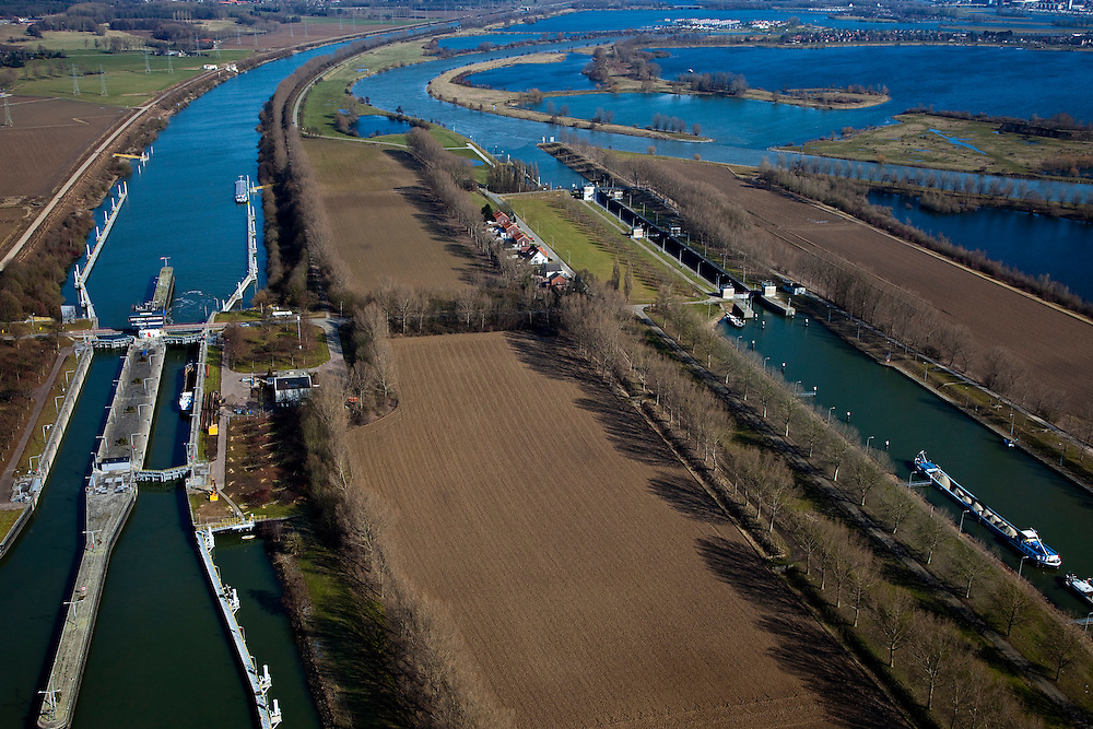 Nederland, Limburg, Gemeente Maasgouw, 07-03-2010; sluiscomplex Heel met links de dubbelsluis van het Lateraalkanaal. Links van het kanaal komt, na de sluis, een retentiegebied voor de opvang van (hoog) water. Rechtsboven de Maasplassen met Roermond aan de horizon..De kleinere sluis (r) geeft toegang tot de Maas naar Roermond. Voor schepen naar het noorden biedt het kanaal een kortere en snellere route dan de oorspronkelijke Maasroute. De aanleg van het sluiscomplex zorgde er voor dat een enorme bocht in de Maas afgesneden kon worden (de Lus van Linne).Lock complex at Heel with double-lock for the Lateral canal (l). Left of the canal, after the lock, a retention area is created for the reception of (high) water..The smaller lock (r) provides access to the Maas to Roermond. For ships to the north, the channel offers a shorter and faster route than the original Maasroute. The construction of the lock complex cut of a huge bend in the Meuse(the Loop of Linne)..luchtfoto (toeslag), aerial photo (additional fee required);.foto/photo Siebe Swart