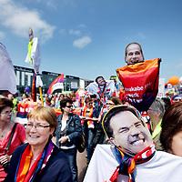 Nederland, Amsterdam , 8 juni 2013.<br /> Landelijke grote manifestatie tegen bezuinigingen in de Zorg.<br /> Vanuit de Czaar Peterstraat arriveerden bussen vol met mensen werkzaam in de zorg om te demonstreren tegen de voorgenomen bezuinigingen in de Zorg. In een protestmars liepen ze gezxamelijk richting het Oosterpark waar de demondtratie plaats vond.<br /> De manifestatie in Amsterdam tegen bezuinigingen in de zorg heeft zaterdag ruim 5000 medewerkers uit de zorg getrokken. Dat meldde een woordvoerster van organisator Abvakabo FNV.<br /> De deelnemers zijn boos over de plannen die de regering heeft met de zorg. Onder het motto 'handen thuis, Rutte!' demonstreren ze tegen de 'afbraakplannen' van het kabinet Rutte.De 5000 zorgmedewerkers komen uit het hele land. Ze verzamelden zich aan de Czaar Peterstraat en liepen vanaf daar naar het Oosterpark, waar de manifestatie werd gehouden. In het Oosterpark ontmoetten de demonstranten in tenten Tweede Kamerleden om over de plannen te praten.'De emoties liepen daarbij soms hoog op', zei de woordvoerster. Ook kwamen enkele sprekers aan het woord, zoals FNV-voorzitter Ton Heerts en SP-leider Emile Roemer. Zanger Gerard Joling verzorgt een optreden. Hij was een van de eersten die zich hardop uitsprak tegen de ideeën van het kabinet, weet Abvakabo FNV.Volgens de bond raken door de plannen van het kabinet 170.000 mensen hun thuiszorg kwijt en verliezen 50.000 thuiszorgmedewerkers hun baan. Nog eens tienduizenden medewerkers in de gehandicaptenzorg en verzorgingshuizen raken zonder werk, concludeert de vakbond.<br /> Op de foto een groep thuiszorg medewerkers uit de Achterhoek demonstreren mee.<br /> Foto:Jean-Pierre Jans