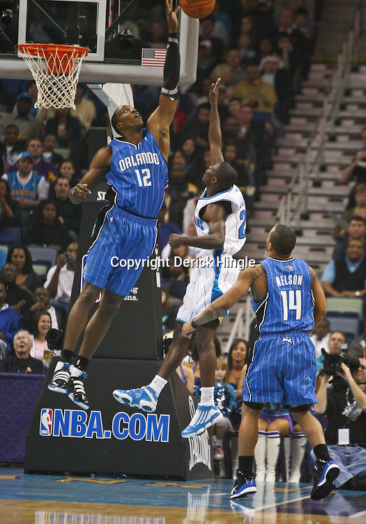 Feb 26, 2010; New Orleans, LA, USA; Orlando Magic center Dwight Howard (12) blocks a shot by New Orleans Hornets guard Darren Collison (2) during the first quarter at the New Orleans Arena. Mandatory Credit: Derick E. Hingle-US PRESSWIRE