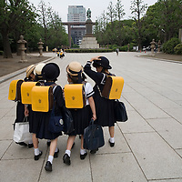 Asia, Tokyo, Japan, Young school girls in uniform walking at Yasukuni Shrine, a memorial to the Japanese dead in WW II