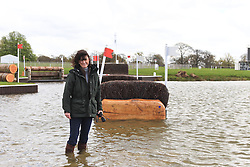 © Licensed to London News Pictures. 30/04/2012. BADMINTON, UNITED KINGDOM. Lucinda Hanbury, one of the Site Directors of The 2012 Mitsubishi Motors Badminton Horse Trials, stands in front of the water jump after it was announced that the event will be cancelled due to poor ground conditions. The event, which was a key qualifier for the 2012 London Olympic Games, has been called off because of large areas of standing surface water and worries about the going of the Cross Country track. Photo credit: Mark Chappell/LNP