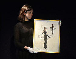 A staff member holds a watercolour and pencil sketch of Audrey Hepburn dressed as Holly Golightly in Breakfast At Tiffany on display ahead of the the Entertainment Memorabilia Sale at Bonhams in Knightsbridge, London later this week.