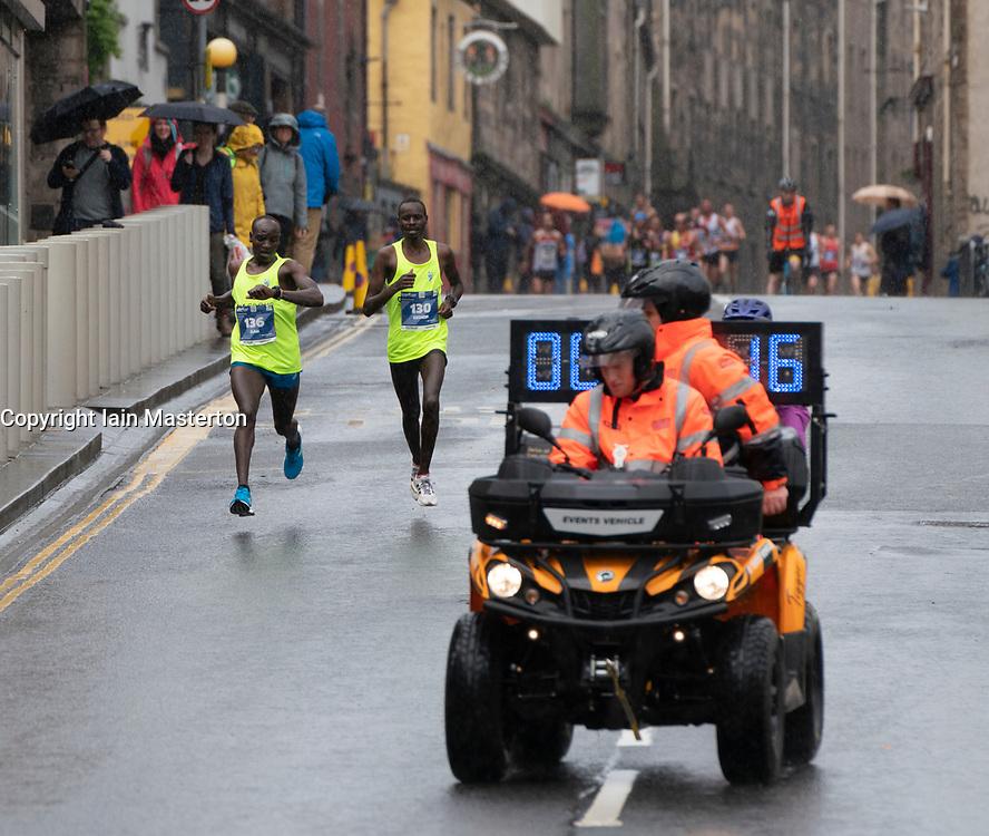 Edinburgh, Scotland, UK. 26 May, 2019. Many runners taking part in the Edinburgh Marathon Festival Marathon run down the Royal Mile in Edinburgh's Old Town towards Holyrood. Pictured; Kenyan Dan Tanui left and Gideon Cheruiyot Kurgat set the early pace