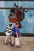Londoners pass-by a large outline of Queen Elizabeth's head in the clothing store Guess in Regent Street, central London ahead of a weekend of nationwide celebrations for the monarch's Diamond Jubilee. A few months before the Olympics come to London, a multi-cultural UK is gearing up for a weekend and summer of pomp and patriotic fervour as their monarch celebrates 60 years on the throne and across Britain, flags and Union Jack bunting adorn towns and villages.