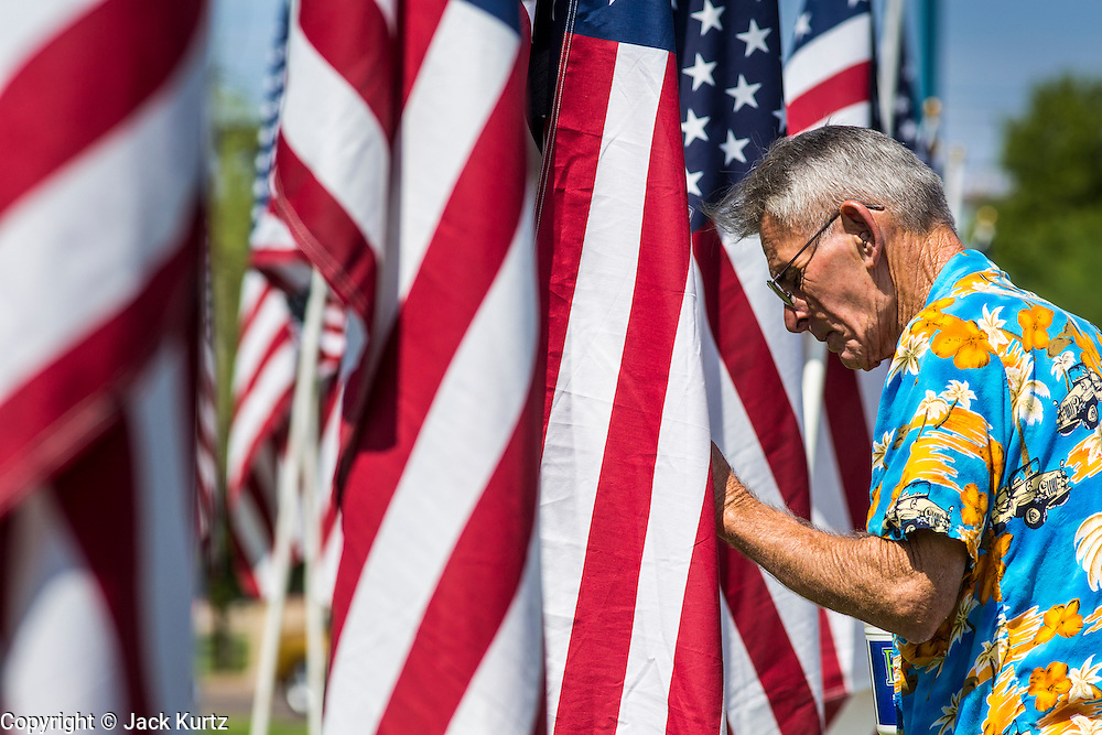 10 SEPTEMBER 2012 - TEMPE, AZ:    A man appears to pray at an American flag at the Healing Field in Tempe, AZ, Monday. The Exchange Club of Tempe and the city of Tempe are hosting the 9th Annual Healing Field display. The annual event posts three thousand American flags in the Tempe Beach Park. The flags are 3?X5?  and stand 8? tall. The display is a tribute to those who died in the terrorist attacks of September 11, 2001. Nearly 3,000 people were killed when terrorists affiliated Al-Qaeda crashed commercial airliners into the World Trade Center in New York, the Pentagon in Arlington, VA, and a field in Ohio.  PHOTO BY JACK KURTZ