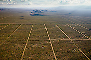 A land-development company has drawn out a grid of roads onto the desert to sell 20-acre lots for speculation. Future homeowners here will have to drill 600-foot wells for water and generate their own electricity.