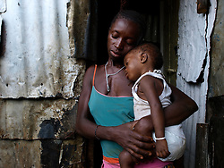 Fatu with one of her tiwn outsides her home in Kroo bay slum. ..Kroo Bay, Freetown, Sierra Leone.